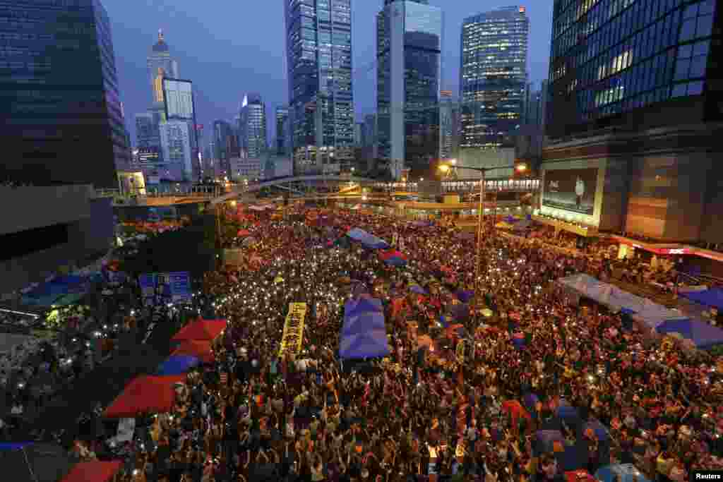 Pro-democracy demonstrators hold banners and shine light from their phones as they mark exactly one month since they took to the streets, in Hong Kong's financial district, Oct. 28, 2014.