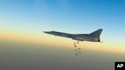 In this frame grab from video provided by the Russian Defence Ministry Press Service, Russian long-range bomber Tu-22M3 flies during a strike above an undisclosed location in Syria, Aug. 14, 2015.