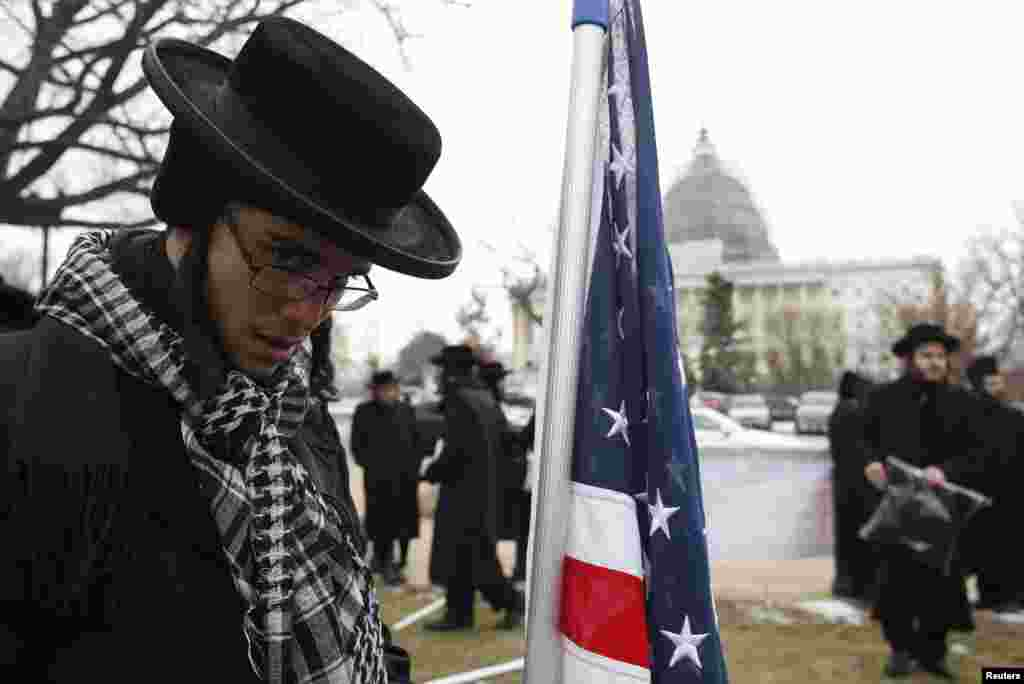An anti-Zionist Orthodox rabbi is pictured next to a U.S. flag during a protest against Israeli Prime Minister Benjamin Netanyahu's speech to a joint meeting of Congress on Capitol Hill in Washington, March 3, 2015.