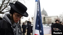 An anti-Zionist Orthodox rabbi is pictured next to a U.S. flag during a protest against Israel's Prime Minister Benjamin Netanyahu's speech to a joint meeting of Congress on Capitol Hill in Washington March 3, 2015. A quarter of Democratic U.S. lawmakers
