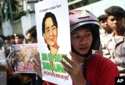 Một nhà hoạt động cầm ảnh lãnh tụ đối lập Aung San Suu Kyi trong cuộc biểu tình đòi chấm dứt bạo lực chống lại người thiểu số Rohingya tại bang Rakhine, bên ngoài sứ quán Myanmar ở Jakarta, Indonesia, ngày 29/5/2015.