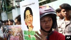 Seorang aktivis memegang poster potret pemimpin oposisi Myanmar Aung San Suu Kyi dalam sebuah protes menuntut diakhirinya kekerasan terhadap etnis Rohingya di negara bagian Rakhine, di luar Kedutaan Besar Myanmar di Jakarta, Indonesia, 29 Mei 2015.