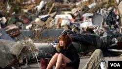 Seorang perempuan duduk menangis di tengah-tengah kerusakan akibat gempa dan tsunami, Senin (14/3).
