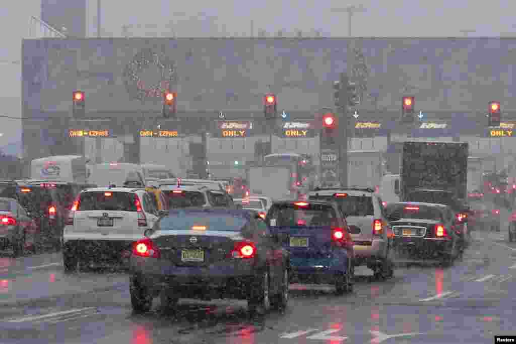 Vehicles wait in line to go through the Holland tunnel to New York City during a snowstorm in Newport, New Jersey, Dec. 10, 2013.