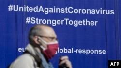 """布魯塞爾一名戴著口罩的行人從歐盟委員會大樓掛有""""全球應對新冠病毒""""字樣的標語前走過。(2020年5月6日)"""