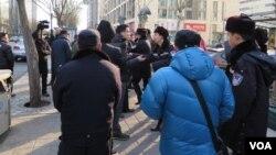 许志永的律师张庆方与庭外外国记者交谈时,受到警察和便衣警察的阻挡,场面一度混乱(美国之音东方拍摄)