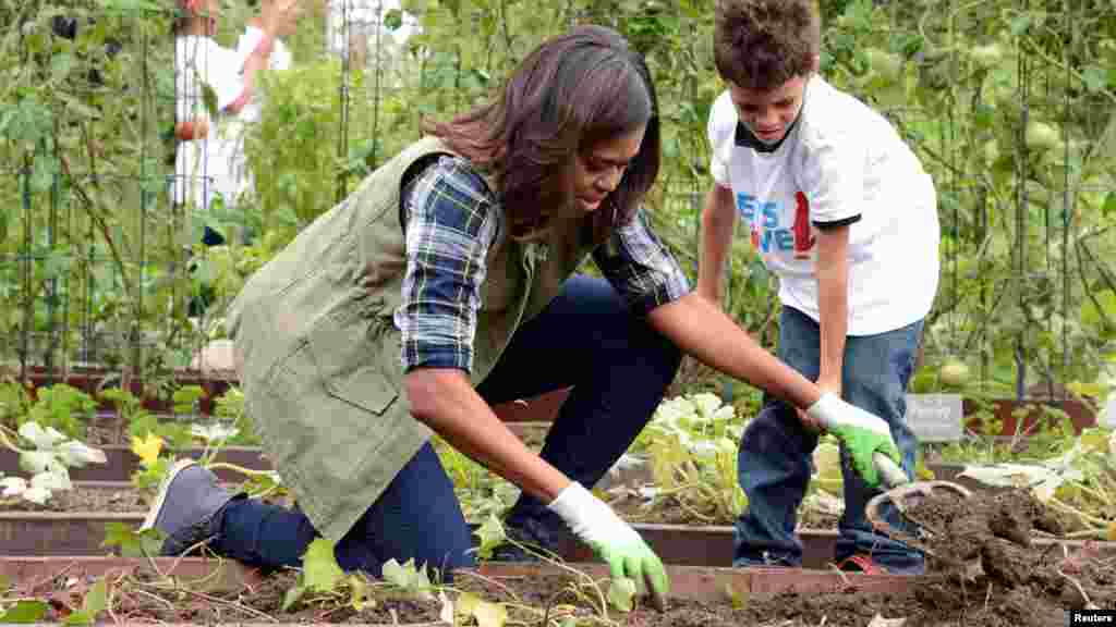 First Lady Michelle Obama helps a youngster harvest vegetables in the White House Kitchen Garden, Oct. 6, 2016.