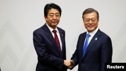 South Korean President Moon Jae-in shakes hands with Japanese Prime Minister Shinzo Abe during their meeting in Pyeongchang, South Korea, Feb. 9, 2018.