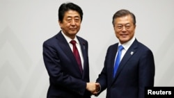 FILE - South Korean President Moon Jae-in shakes hands with Japanese Prime Minister Shinzo Abe during their meeting in Pyeongchang, South Korea, Feb. 9, 2018.