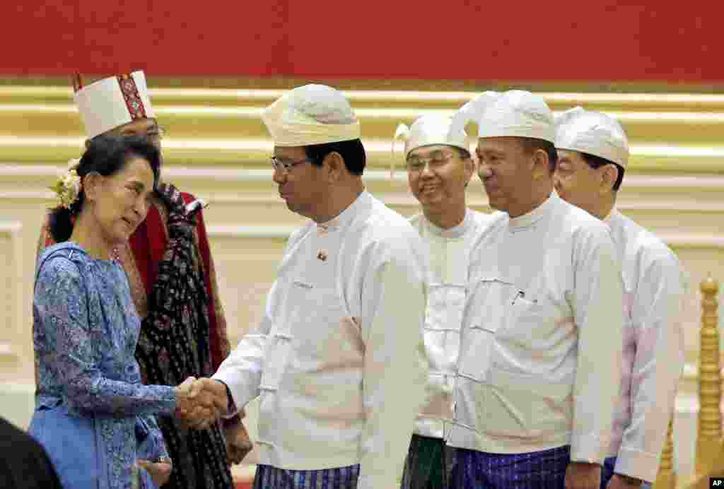 Aung San Suu Kyi, left, greets members of Myanmar's old cabinet during a presidential handover ceremony in Naypyitaw.