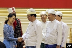 Aung San Suu Kyi, left, greets members of Myanmar's old cabinet during a presidential handover ceremony in Naypyitaw, Myanmar, March 30, 2016.