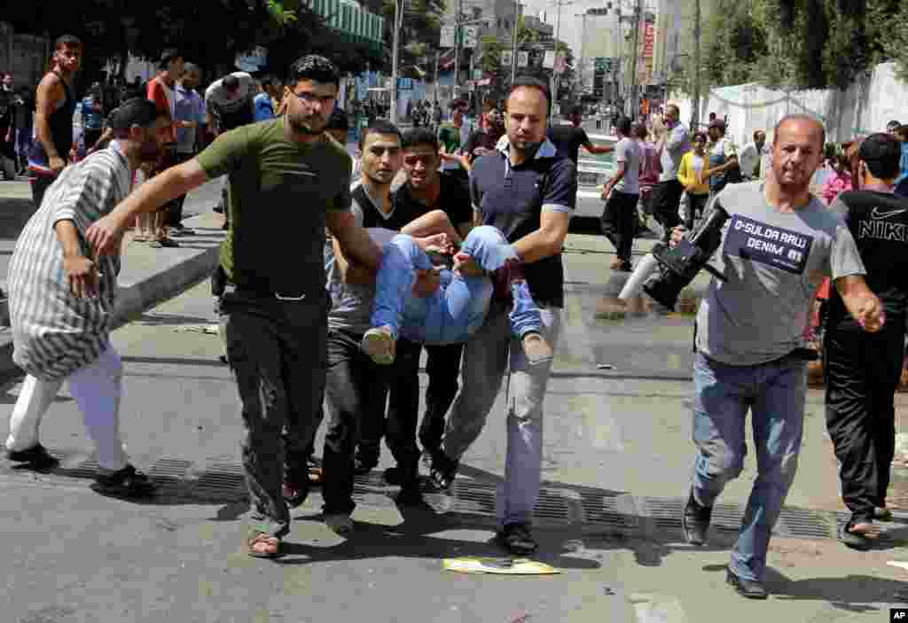 Palestinians carry a person killed in a blast outside a U.N.-run school in Rafah, in the southern Gaza Strip, Aug. 3, 2014.