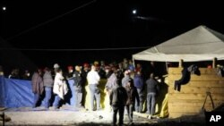 Rescue workers and miners stand at a mine where an explosion occurred in San Juan Sabinas, in the Mexican State of Coahuila, May 4, 2011