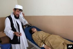 FILE - An Afghan patient is seen on the bed as a father weeps in the Mental Health and Drug Addicts' Hospital in Kabul, Afghanistan.