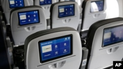 This March 16, 2017, photo shows the interior of a JetBlue airliner at John F. Kennedy International Airport in New York. Government figures show that U.S. airlines are improving at flying on time, handling baggage and not bumping as many passengers. Complaints are down too.