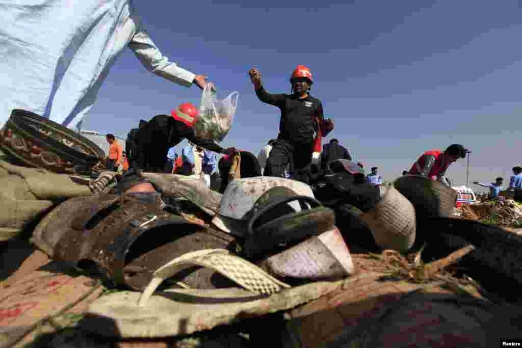 Rescue workers are seen collecting evidence behind footwear, after a bomb blast at a vegetable and fruit market in the outskirts of Islamabad, April 9, 2014.