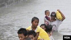 Warga menggendong anak-anak mereka saat melintasi daerah mereka yang terendam banjir akibat topan Nesat (Pedring) di desa Tanza, Malabon, utara Manila (27/9).