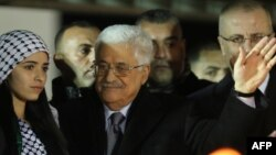 Palestinian president Mahmud Abbas, center, waves to the crowd during a gathering to celebrate the 50th anniversary of the start of the Fatah movement, in the West Bank city of Ramallah, Dec. 31, 2014.