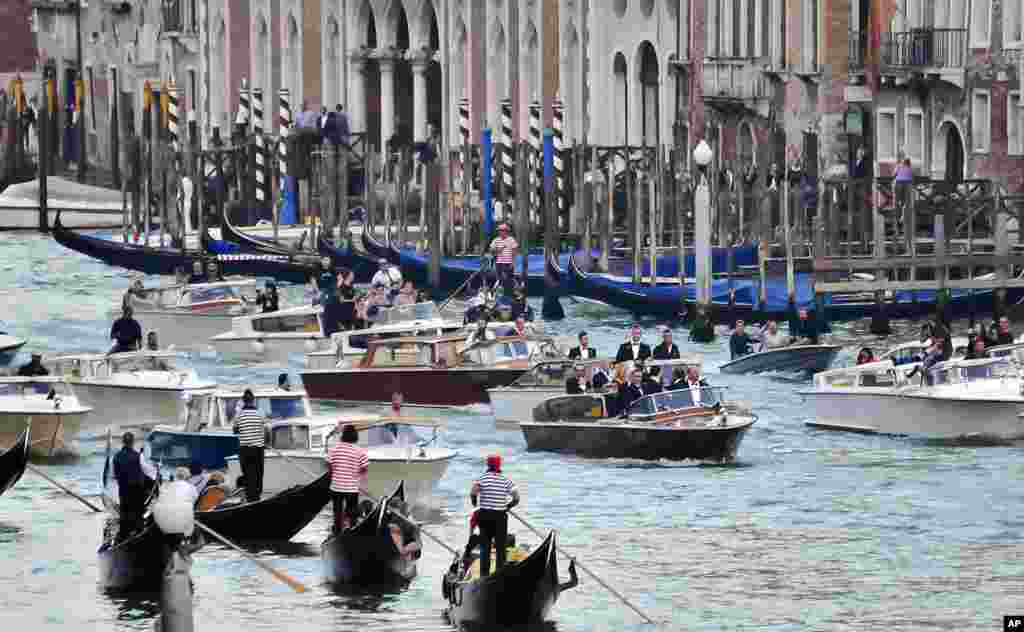 The boat carrying actor George Clooney and his guests cruises in front of media boats in the Grand Canal on its way to the Aman hotel ahead of his wedding in Venice, Sept. 27, 2014.