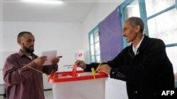 Громадянин Тунісу готується вкинути бюлетень до урни для голосування. В Тунісі відбуваються перші за більш ніж пів століття вільні вибори.