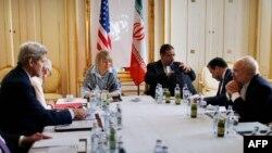ລັດຖະມົນຕີຕ່າງປະເທດສະຫະລັດ ທ່ານ John Kerry (ຊ້າຍ), ລັດຖະມົນຕີຕ່າງປະເທດອີຣ່ານ ທ່ານ Mohammad Javad Zarif (ຂວາມື ຄົນທີສອງ), ປະຊຸມກັນ ຢູ່ທີ່ໂຮງແຮມ ແຫ່ງໜຶ່ງ ໃນນະຄອນຫຼວງ Vienna, ວັນທີ 27 ມິຖຸນາ 2015.