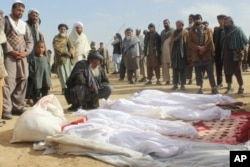FILE - Afghan villagers gather around the bodies of several people who were killed during clashes between Taliban and Afghan security forces in Taliban-controlled Buz-e Kandahari village in Kunduz province, Afghanistan, Nov. 4, 2016.