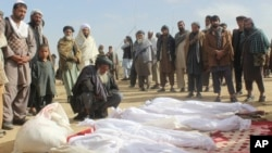 Afghan villagers gather around several victims' bodies who were killed during clashes between Taliban and Afghan security forces in Taliban's controlled village, Buz-e Kandahari village in Kunduz province, north of Kabul, Afghanistan, Friday, Nov. 4, 2016.