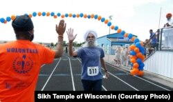 "A man completes the Sikh Temple of Wisconsin's 6k ""Chardhi Kala"" Run with a high five."
