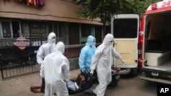Hindistanda Mumbayda təcili yardım işçiləri xəstələri xəstəxanaya aparır.