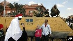 Photo de famille devant un tank sur la place Tahrir, au Caire