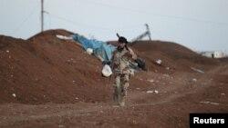 Seorang tentara pemberontak Suriah dari kelompok Jaysh al-Sunna membawa makanan di bagian selatan kota Aleppo, Suriah (foto; dok).