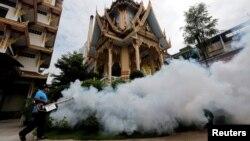 Một người công nhân phun thuốc diệt muỗi tại một ngôi đền thuộc thủ đô Bangkok, Thái Lan.