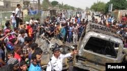 Warga berkumpul di dekat serangan bom di kota Sadr, Baghdad (16/5). Sedikitnya 11 orang tewas dan 18 orang dilaporkan terluka dalam serangan ini.