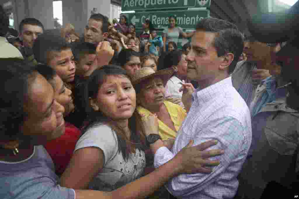 In this photo released by Mexico's presidential press office, Mexican President Enrique Pena Nieto meets with people affected by Tropical Storm Manuel in the Pacific coast city of Acapulco, Mexico, Sept. 16, 2013.