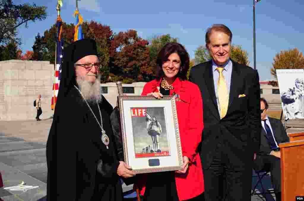 Η κόρη του τιμηθέντα Μιχάλη Κόκκινου παραλαμβάνει το βραβείο, εκ μέρους του πατέρα της, από τον Αρχιεπίσκοπο Αμερικής και τον Πρόεδρο του Ιδρύματος ΟΧΙ