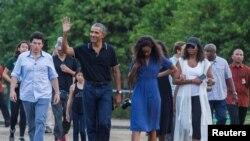 Mantan Presiden AS, Barack Obama, melambaikan tangan saat berjalan bersama putrinya, Mali, dan istrinya Michelle selama kunjungan ke Candi yang berasal dari abad ke-9, Borobudur, di Magelang, Indonesia tanggal 28 Juni 2017 (foto: REUTERS/Pius Erlangga)
