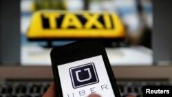 Le logo uber sur le téléphone portable et le signe d'un taxi, le 15 septembre 2014.