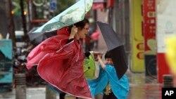 Seorang perempuan dan anaknya memegang payung mereka dengan erat, saat angin kencang yang dipicu oleh topan Usagi bergerak mendekati Taipei, Taiwan (21/9).