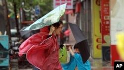 A woman and her child hold their umbrellas tight against powerful gusts of wind as Typhoon Usagi approaches in Taipei, Taiwan, Sept. 21, 2013.