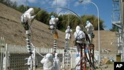 ພວກຄົນງານພວມຕໍ່ສາຍໄຟຟ້າ ເຂົ້າໄປໃສ່ໂຮງໄຟຟ້ານິວເຄລຍ Fukushima Daiichi ທີ່ໄດ້ຮັບຄວາມເສຍຫາຍ (24 ມີນາ 2011)