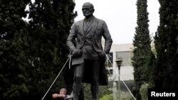 Tượng cựu Tổng thống Mỹ Harry Truman bị người Cộng sản Hy Lạp biểu tình buộc dây thừng và dùng cưa sắt cắt chân để tìm cách giật đổ trong cuộc biểu tình phản đối Mỹ tấn công Syria hôm 16/4/2018 ở Athens.