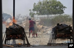 Family members of COVID-19 victims leave as their funeral pyres burn at an open crematorium set up at a granite quarry on the outskirts of Bengaluru, India, Wednesday, May 5, 2021. (AP Photo/Aijaz Rahi)