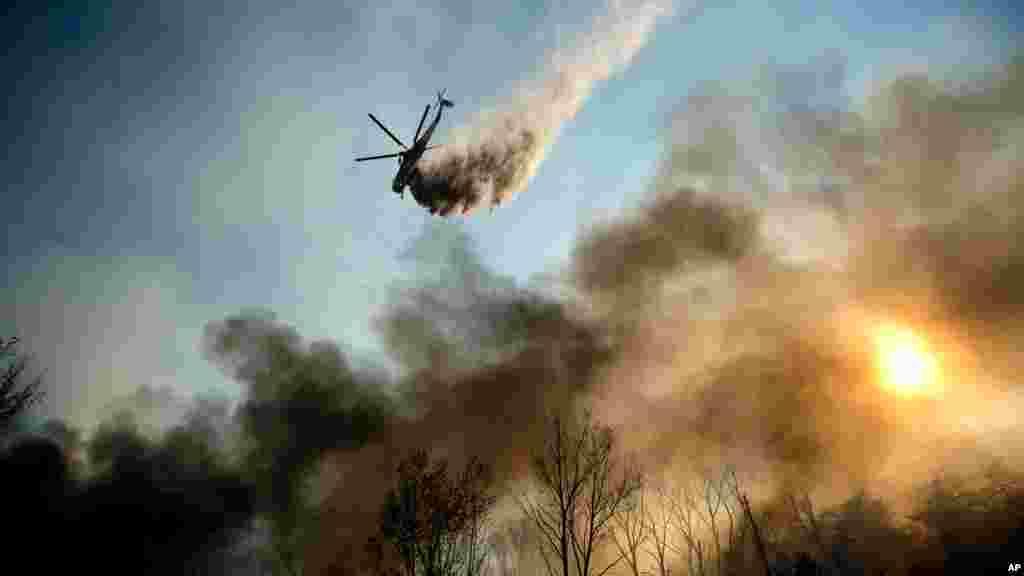 Un hélicoptere largueun liquide ignifugeàLytle Creek (Californie) pour limiter la propagation de l'incendie Blue Cut, le17 août 2016.