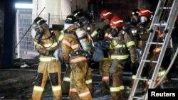 韩国消防人员在堤川市火灾现场救护受难者。(2017年12月21日)