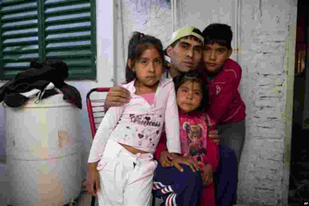 Cristian Marcelo Reynoso, center, poses inside his home with his children, Milagro, 5, left, Oriana, 3, bottom, and Nahuel, 10, right, in their home in the Villa 21-24 slum in Buenos Aires, Argentina, March 14, 2013. At Villa 21-24, a slum so dangerous that most outsiders wouldn't dare go in, Jorge Mario Bergoglio often showed up unannounced to share laughs and sips of mate, the traditional Argentina herbal tea.