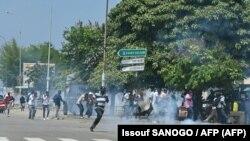 Des partisans de l'ancien président ivoirien Laurent Gbagbo affrontent la police anti-émeute à Abidjan, le 17 juin 2021, avant son arrivée dans le pays.