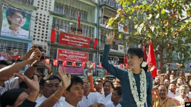 Burma's pro-democracy leader Aung San Suu Kyi waves at supporters during the opening ceremony of the National League for Democracy party's Mingalar Taung Nyunt township office in Rangoon, January 17, 2012.
