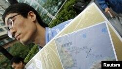 Seorang aktivis Korea Selatan menunjukkan gambar peta pulau Dokdo yang dihapus namanya dalam fitur aplikasi peta baru keluaran Apple dan Google (foto: dok).