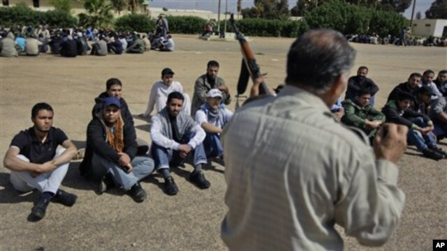 New recruits listen as a training instructor schools them in disassembling, cleaning, and use of AK47 automatic weapons, at a rebel forces training camp in Benghazi, Libya, April 5, 2011