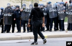 FILE - A demonstrator clutching a brick faces a line of police officers amid tension after Freddie Gray's funeral in Baltimore, April 27, 2015.